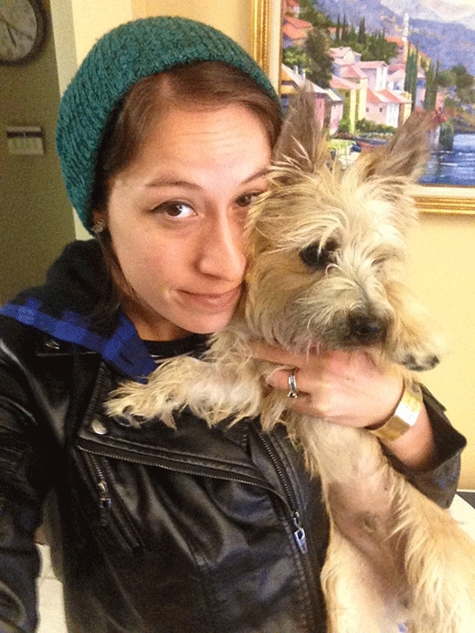 Woman in black leather jacket and green beanie holding her brown terrier.